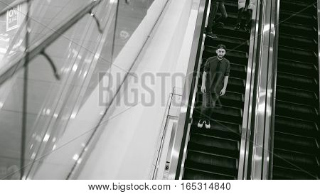 Young Man With A Beard In A Plaid Shirt And A Tie And Cap, Riding On An Escalator In The Mall