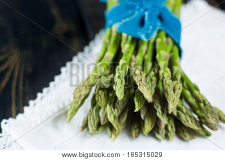 Spring season - fresh green asparagus on black wooden background