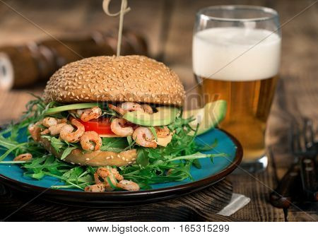 Close up burger with prawns grilling on a wooden board with a glass of lager