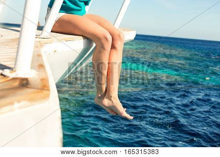 Young woman sitting on the ship deck enjoying the moment on a sunny day. Copy space