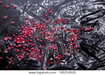 red berries on a dark background with flour top view cranberries