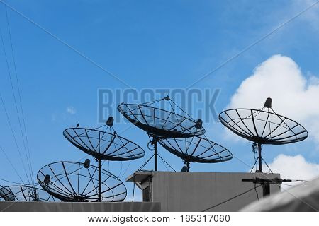 Many satellite dishes on roof top, with blue sky