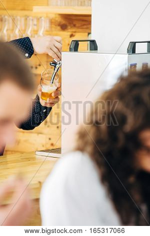 Mans hands pouring glass with craft beer