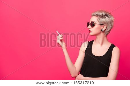 Stylish sensual young woman with short blond hairstyle smoking a cigarette. High fashion girl in round sunglasses looking to copy space over pink color background