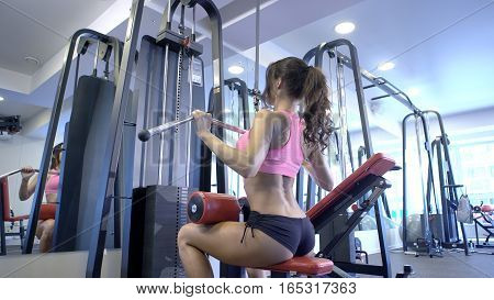 Back view. Portrait of young woman working out on exercise machine inside gym light room background. Woman doing seated exercises at a gym