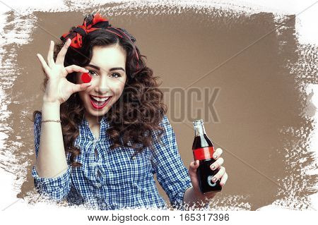 Playful curly brunette holding cup of glass bottle. Girl clothed red scarf and plaid shirt. Text place paper background.