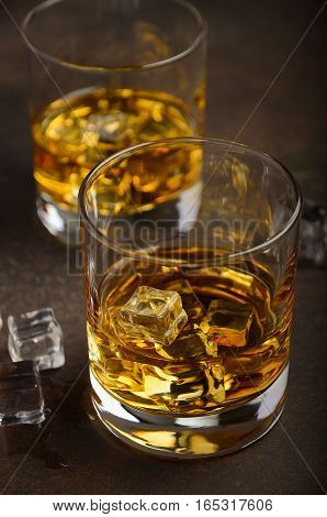 Glass of whiskey with ice on the old rusty background, selective focus