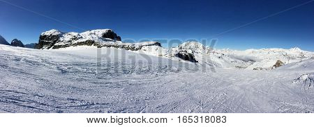 panoramic mountain landscape in winter under blue sky