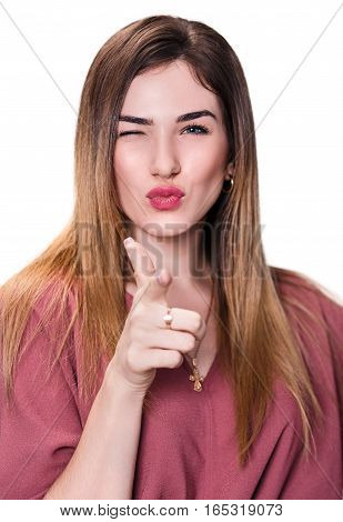Young woman winks and point at you over white background