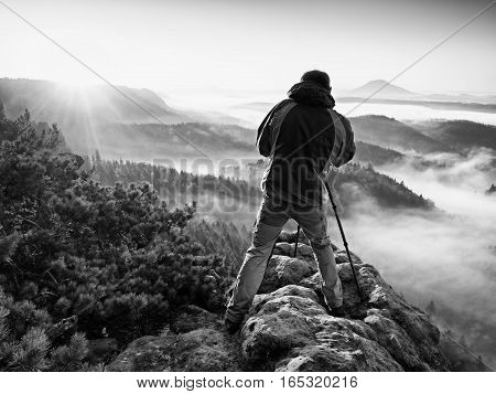 Photograph silhouette take photo. Man enjoy photography of fall daybreak in nature on cliff on rock. Autumnal foggy landscape misty sunrise.