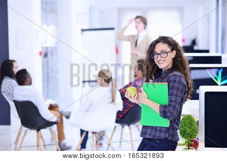 business, startup and people concept - happy creative team with computer and folder in office.