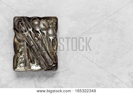 Various silverware in a metal tray on the background of gray concrete surface; with copy-space