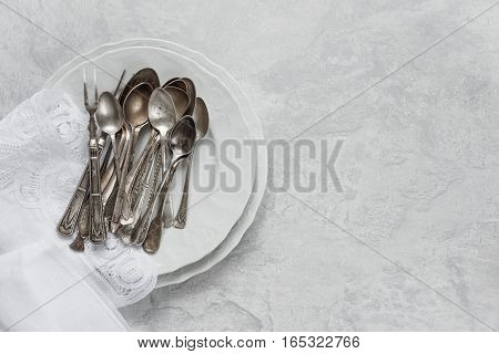Various silverware on a porcelain plate and white napkin with Belgian lace are on the background of gray concrete surface with copy-space