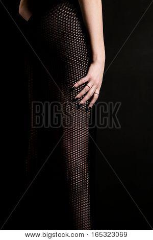 Female leg in a transparent dress on a dark background