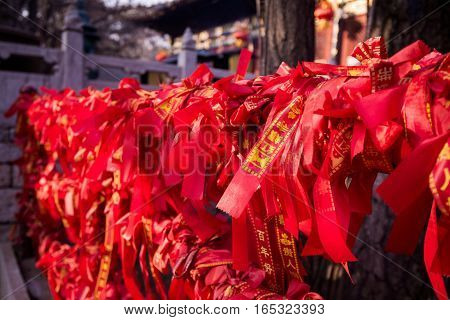 Chinese red ribbons on a fence in Buddhist temple