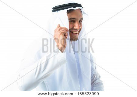 studio shot of young man wearing traditional arabic clothing, talking on phone