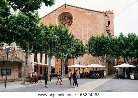 Pollensa Mallorca Spain: May 24 2016: Young men play football against Church of Our Lady of the Angels on Main Square Plasa Major of Pollensa