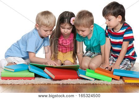 Group of four children with books sits on the floor