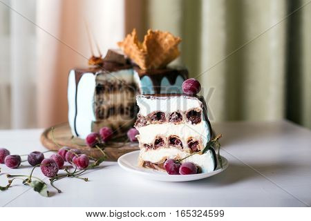 Cut cherry cake decorated with waffles and caramel on a dark wooden background