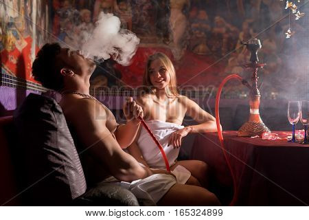 Sexy beautiful long haired blonde in bikini and young tattoed man in white briefs smoking hookan in sauna rest room with luxurious interior