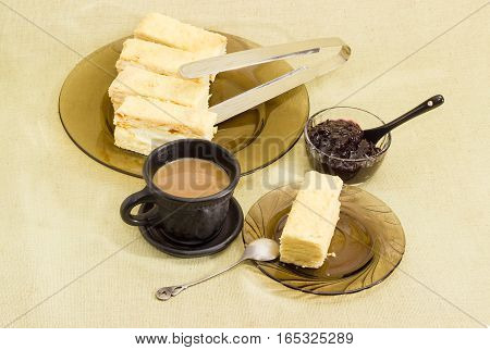 Piece of layered sponge cake on a glass saucer with spoon several pieces of the rest of the cake on glass dish coffee with milk in black cup and small glass bowl with jam on a cloth surface