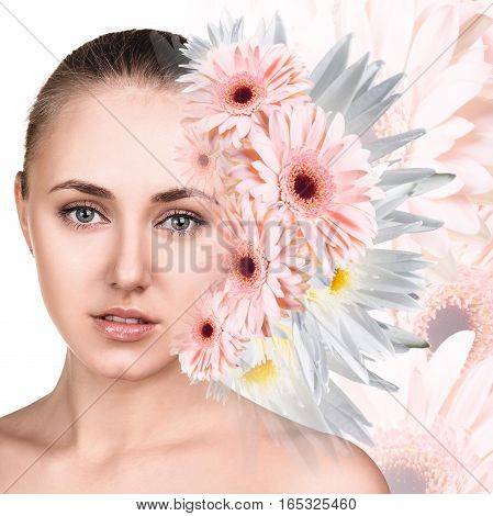 Young attractive woman with clean skin appears from bouquet flowers over white background.
