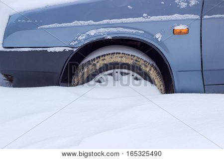 Fragment of the snow covered blue car with a front wheel tire covered with mud