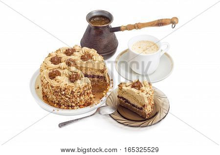 Partly sliced layered sponge cake decorated with butter cream caramelized condensed milk and nuts white cup of a coffee with cream freshly brewed coffee in old coffee pot on a light background