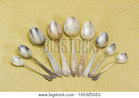 Several old spoons different sizes made from stainless steel and nickel silver on cloth surface
