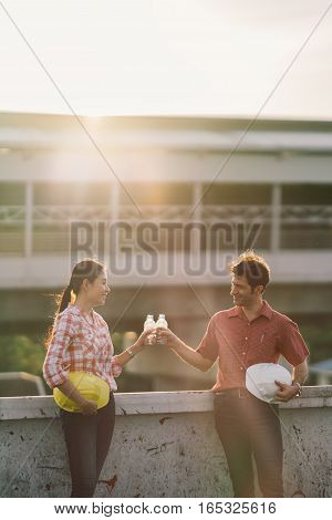 Two construction engineers celebrate after work or project at construction site or factory at sunset rim light and sun flare effect man and woman bumping water bottles success or industrial concept