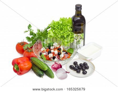 Greek salad in a glass salad bowl among ingredients for its cooking on a white background.