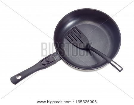 Cast frying pan made of aluminium alloy with removable handle and plastic spatula on a light background