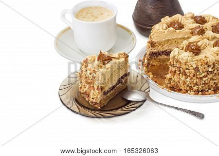 Partly sliced layered sponge cake decorated with butter cream caramelized condensed milk and nuts on background of coffee cup and coffee pot on a light background
