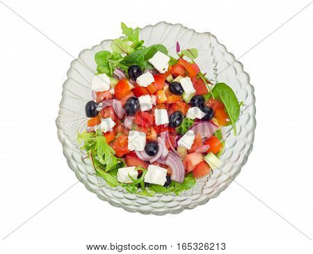 Top view of greek salad in a glass salad bowl on a white background