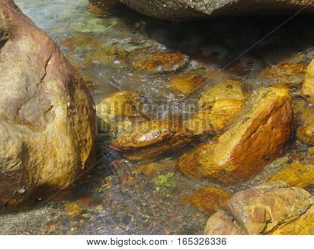 Different Size And Color  Boulders, With Back Ground Water