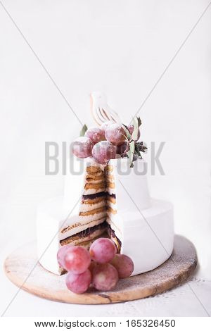 Cut cake souffle on a white background with white decor and grapes