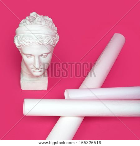 Marble head of young woman, ancient Greek goddess bust with paper rolls or scrolls on pink background. Architecture project, art, building, construction, real estate concept.