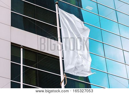 White flag waving in the wind with office building in the background. Perfect mockup to add any logo symbol or sign