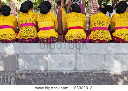 Group of beautiful Balinese women in costumes - sarong waiting for Hindu ceremony in temple. Traditional dance art festivals culture of Bali island and Indonesia people. Indonesian travel background