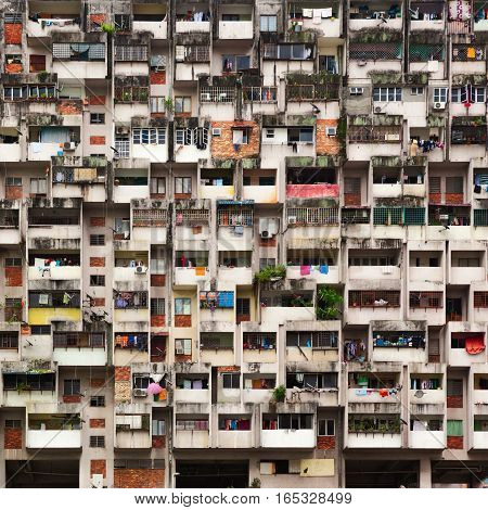 Geometrical pattern of multistory apartment house with group of windows and tenant lumber on balconies. Asian cities street background. Cheap accommodation social problems in overcrowded countries.