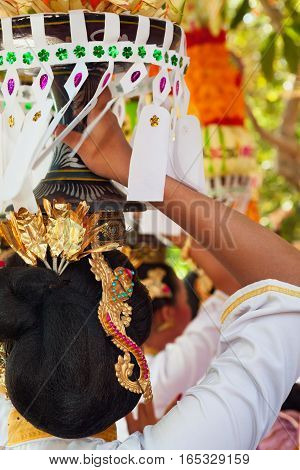 Group of beautiful Balinese women in costumes - sarong carry offering for Hindu ceremony. Traditional dances arts festivals culture of Bali island and Indonesia people. Indonesian travel background