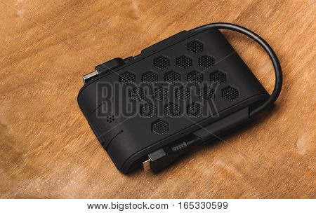 The external hard drive of black color lies on the wooden desktop. Side view on top