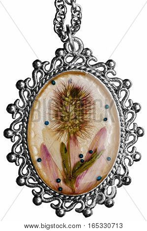 The medallion of handwork is made of epoxy and the dried plants in a silver frame. The pendant is isolated on a white background.
