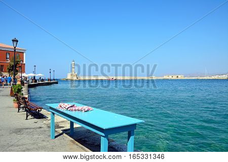 CHANIA, CRETE - SEPTEMBER 16, 2016 - View of the Venetian lighthouse at the harbour entrance with a table at the waterside the promenade in the foreground Chania Crete Greece Europe, September 16, 2016.