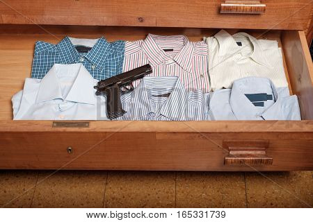 Gun hidden in a drawer full of shirt at home poster