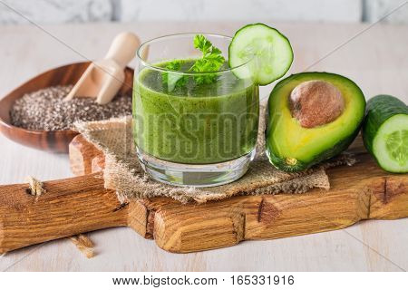 Healthy green juice smoothie surrounded by avocado, cucumber,  celery and chia seeds on white background