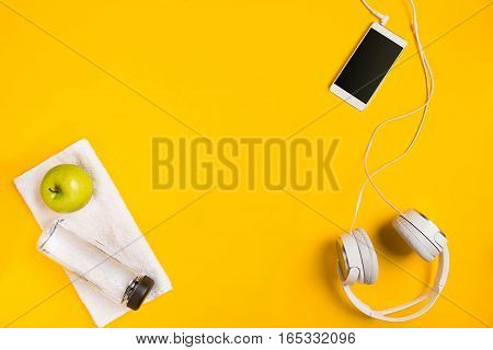 Athlete's set with smart, headphones and bottle of water on yellow background. Top view. Still life