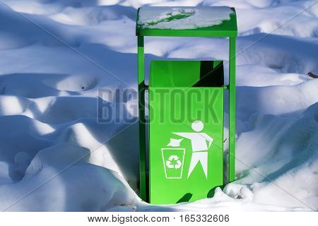 Green trash can with recycle sign in the snow