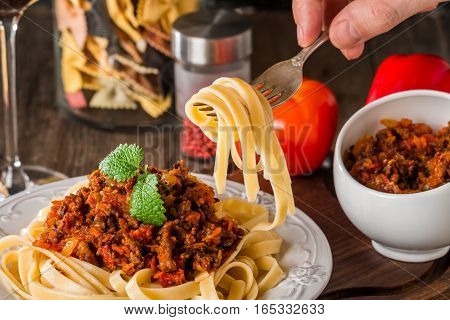 Spaghetti Bolognese on white plate with hand holding a fork with pasta, wooden background