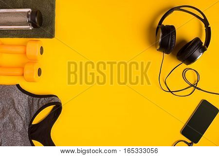 Athlete's set with female clothing, dumbbells and bottle of water on yellow background. Top view. Still life
